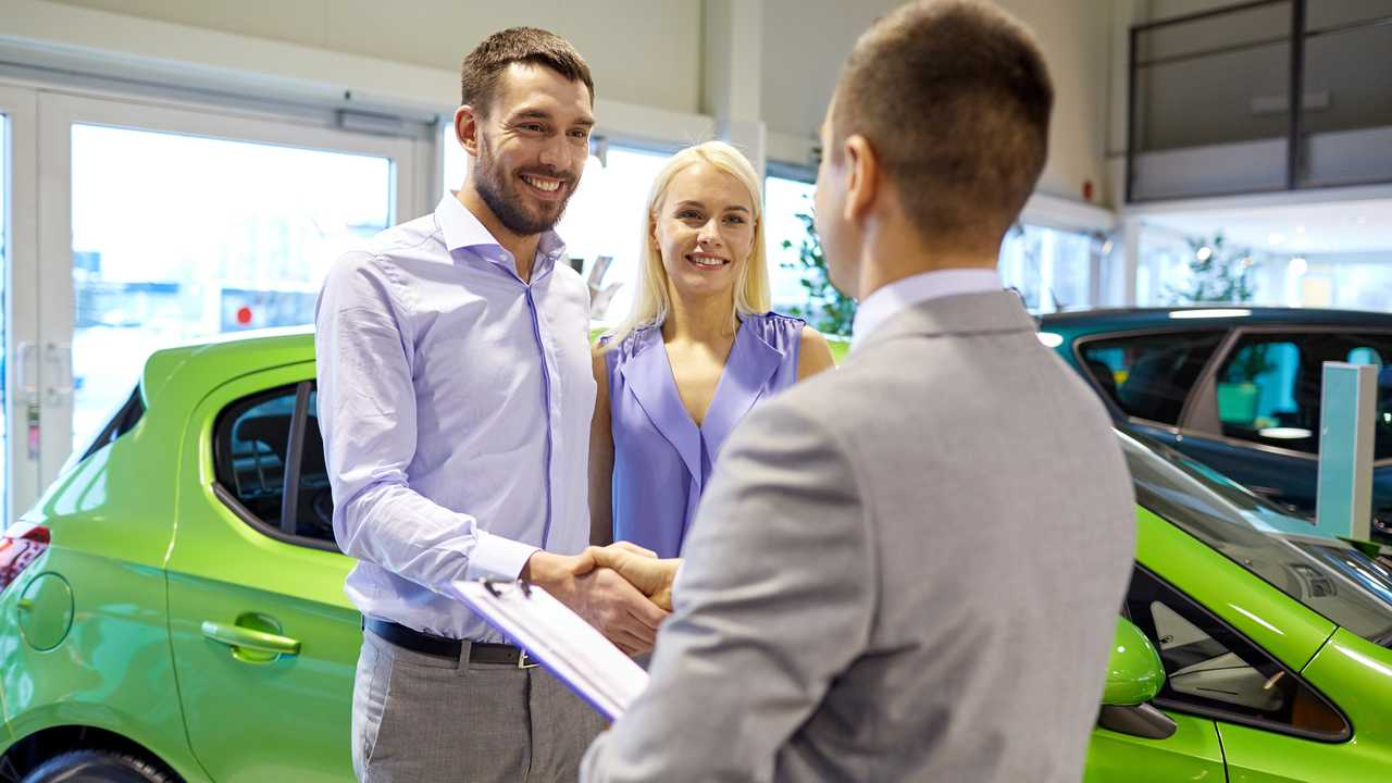 Happy couple with dealer shaking hands in car showroom
