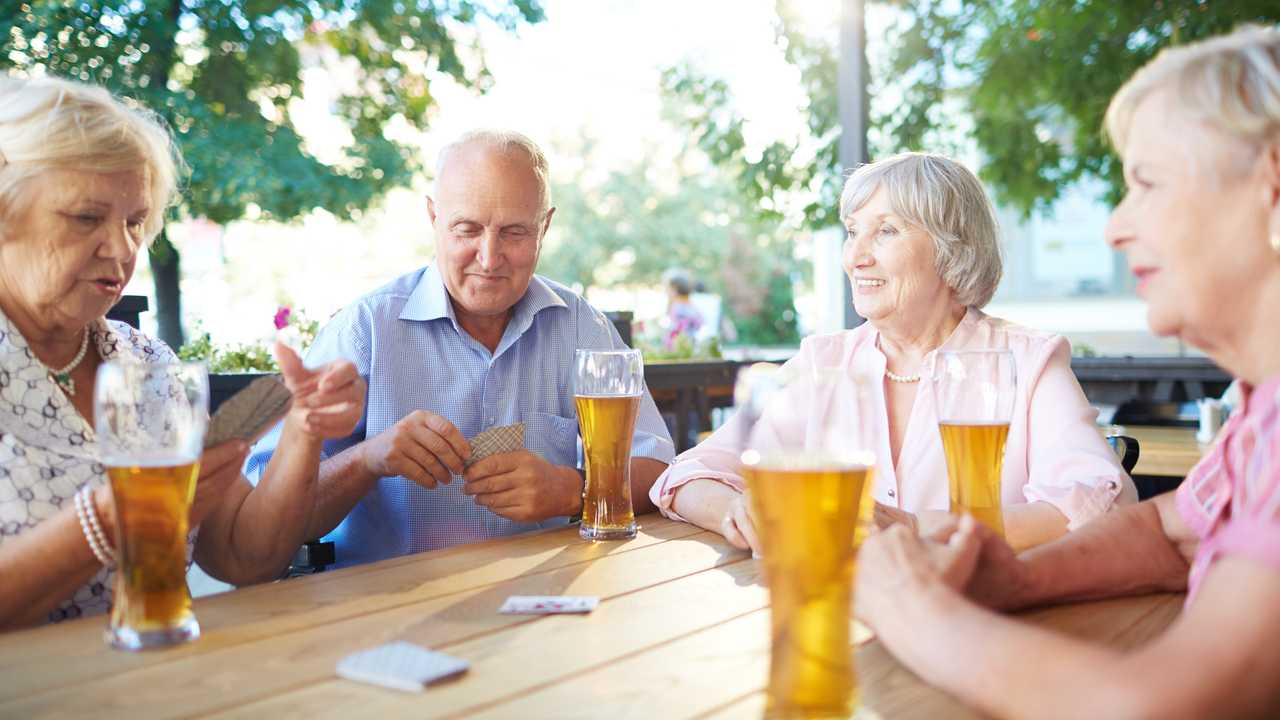 Seniors in a pub drinking beer and playing cards