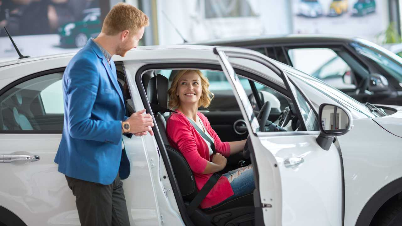 Happy woman customer in showroom sitting in car with salesman