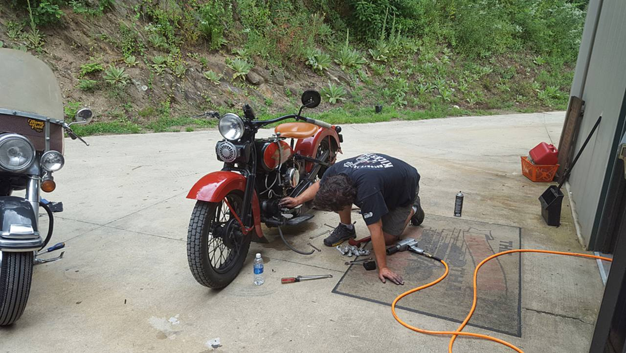 Who wants to work on their bike at home, when they can crawl around in a hot parking lot?