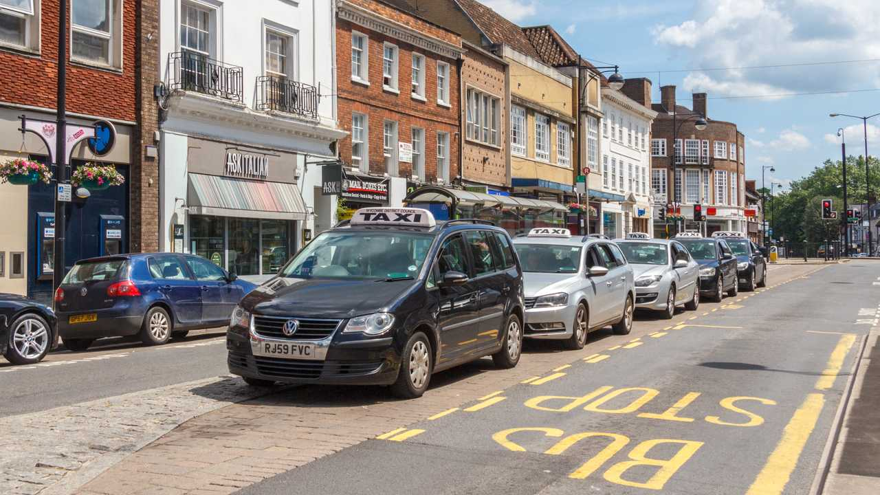 Taxi cabs lines up at a taxi rank on High street in High Wycombe