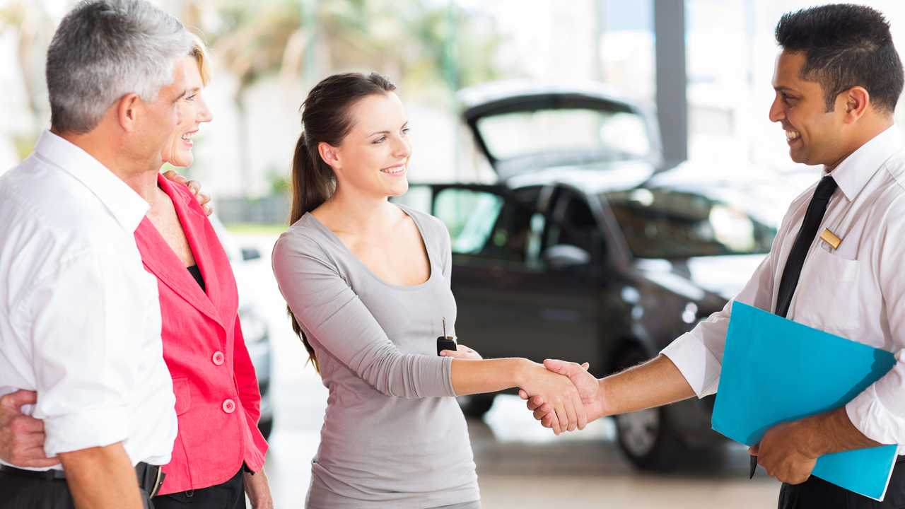 Car salesman shaking hands with young adult customer with parents