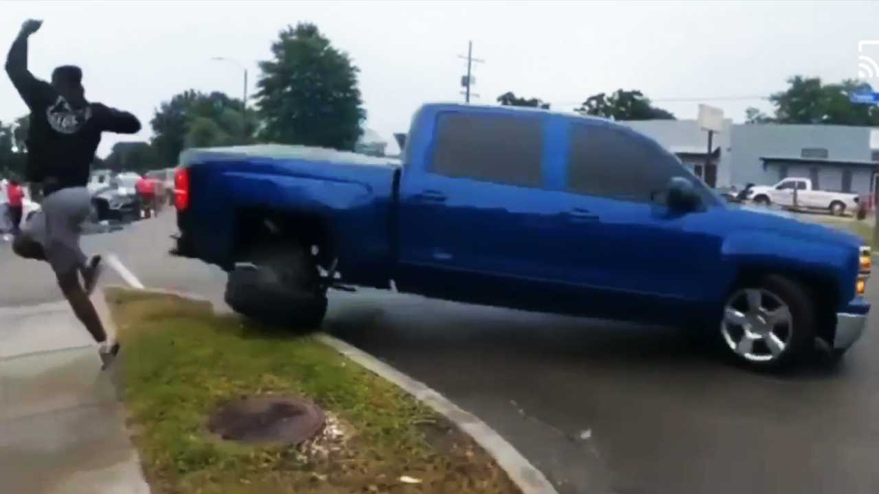 A Chevrolet Silverado pickup truck hits a curb trying to drift in public.