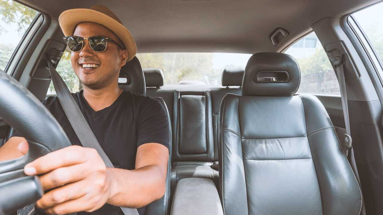 Smiling young man driving car