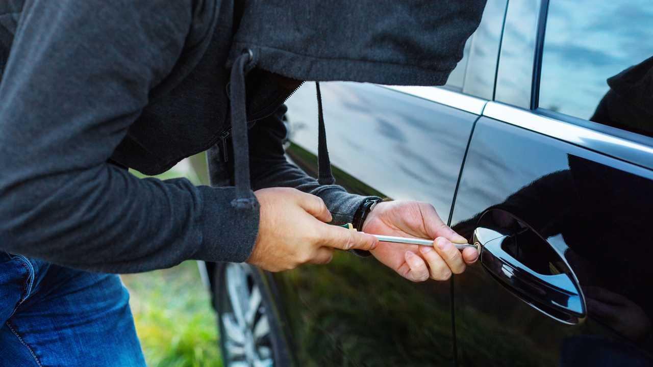 Man breaking into car door with screwdriver