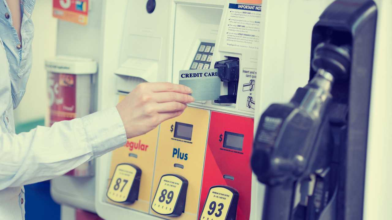 Woman swiping credit card at petrol station fuel pump