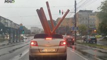 Renault Megane Cabrio transportiert Rohre im rumänischen Regen