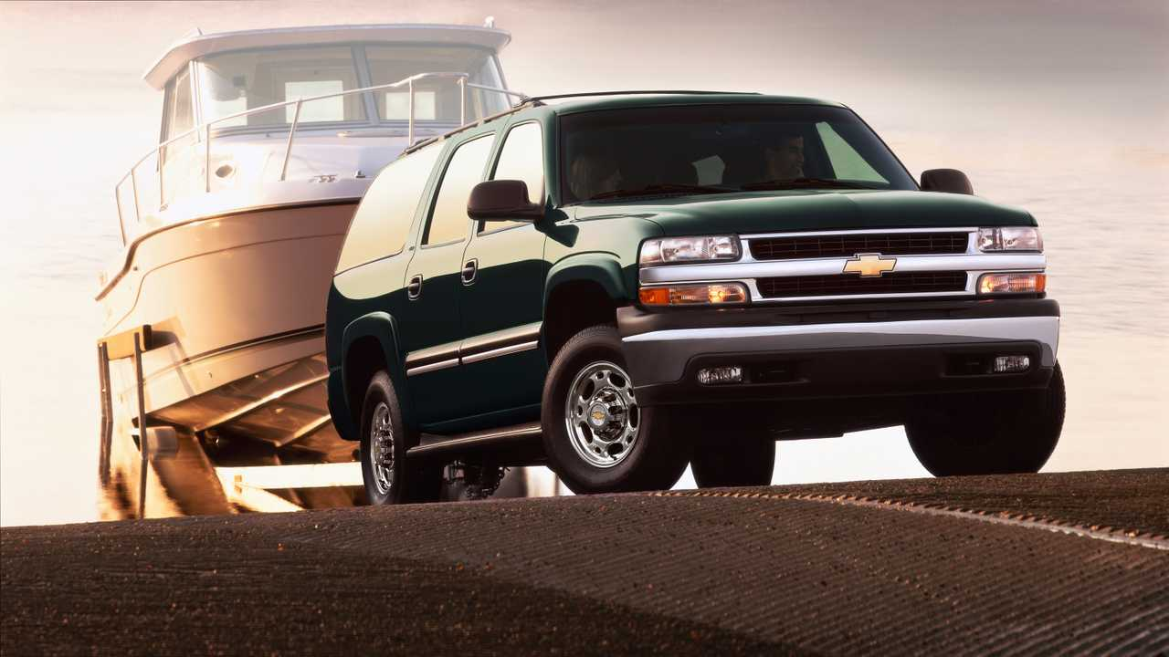 A 2002 Chevrolet Suburban towing a boat.