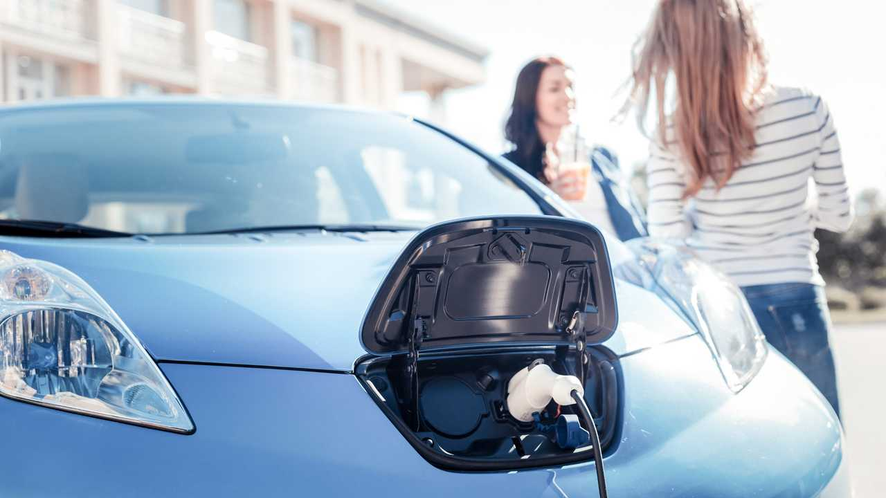 Nissan Leaf charging with young women standing near