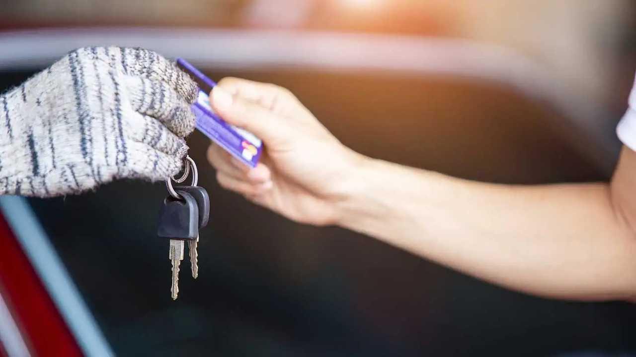 Tangan bertukar kunci mobil dan kartu kredit untuk perbaikan mobil