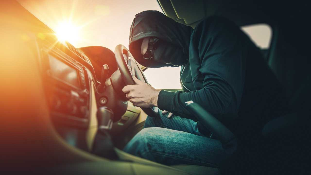 Car thief in car wearing a black mask and glasses