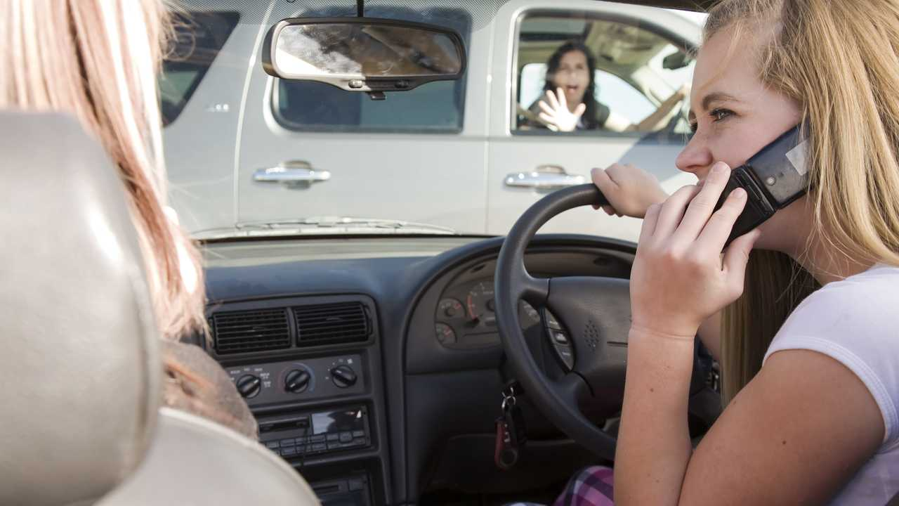 Distracted teenage girl using phone while driving causing a collision