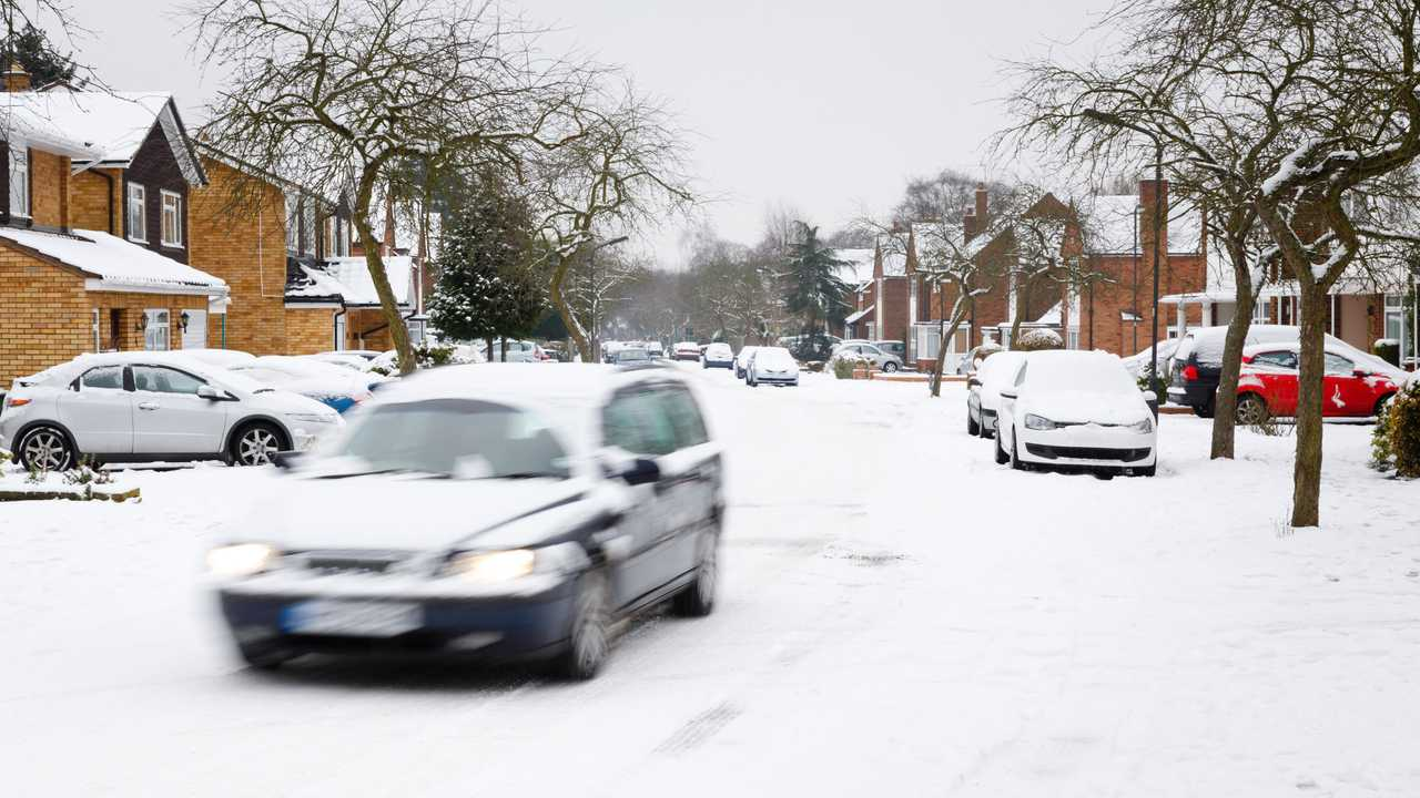 Car driving in snow covered UK residential neighbourhood