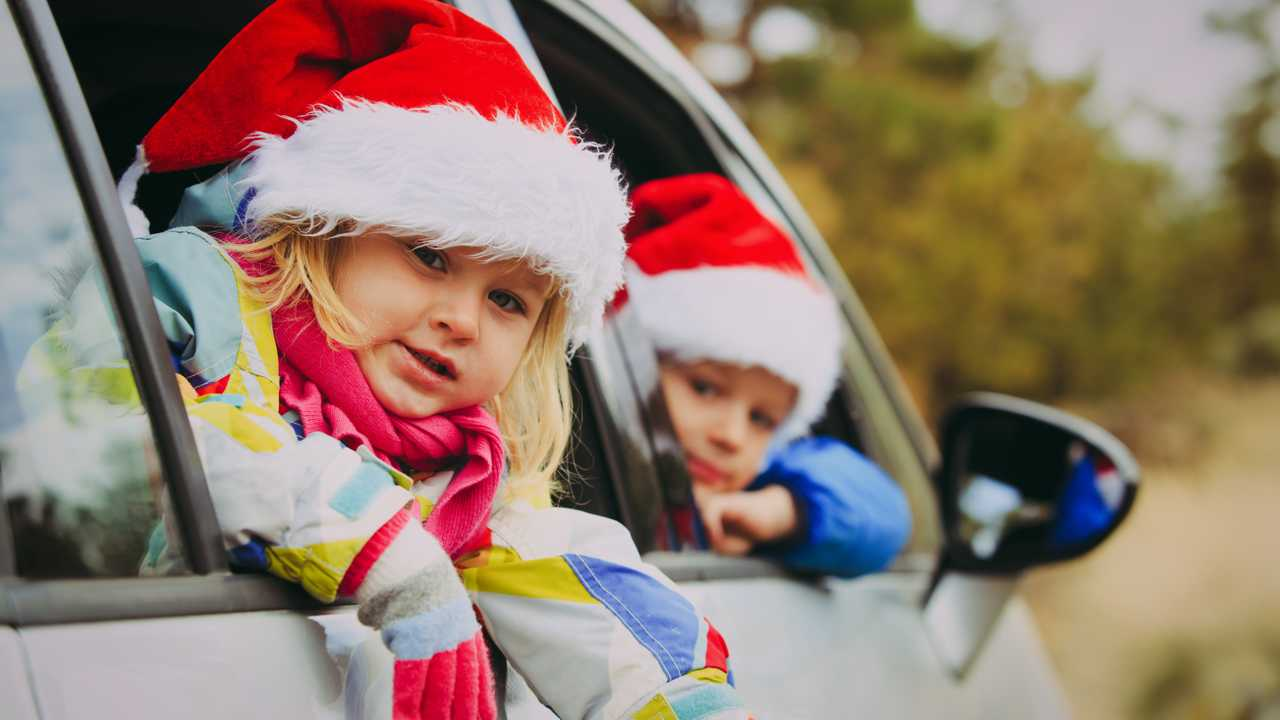 Winter driving with kids in car wearing Christmas hats