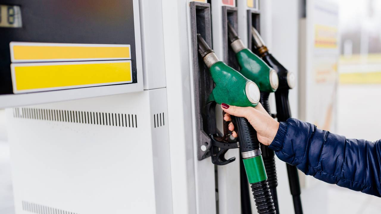 Woman holding fuel nozzle at petrol station