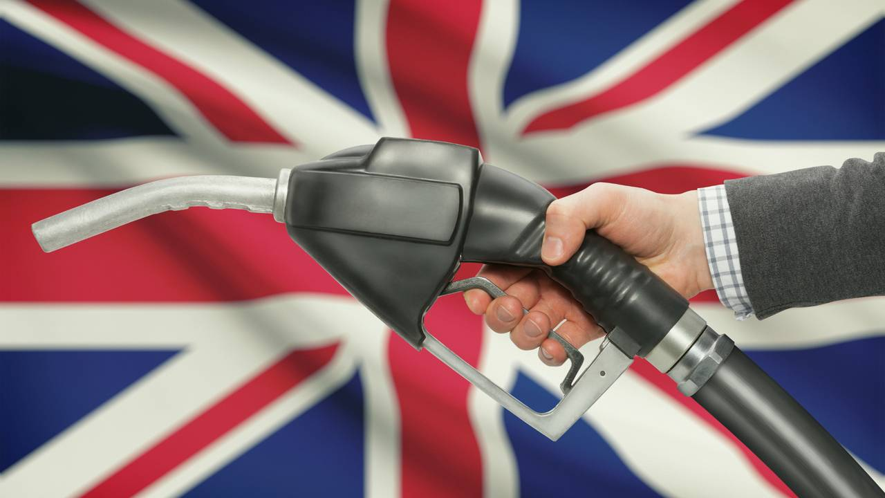 Fuel pump nozzle in hand with Union Jack flag in background