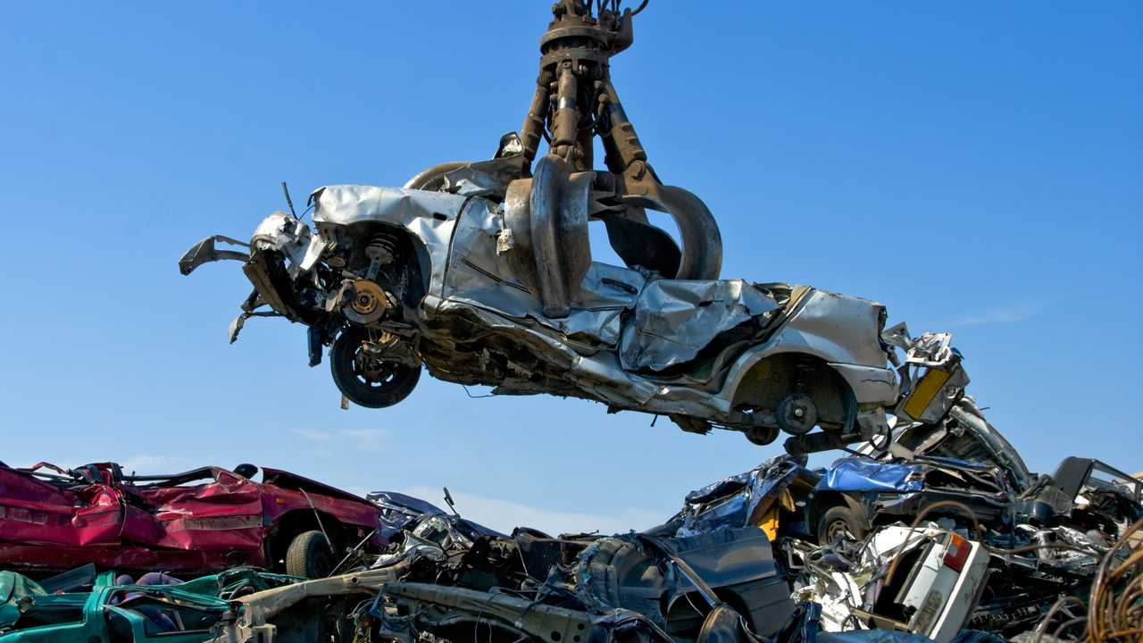 Crane picking up a car in a junkyard