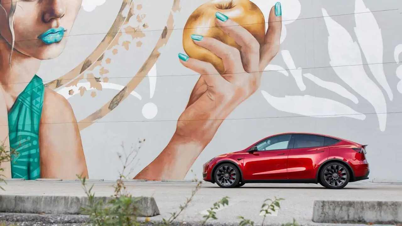 Tesla Model Y in front of graffiti art