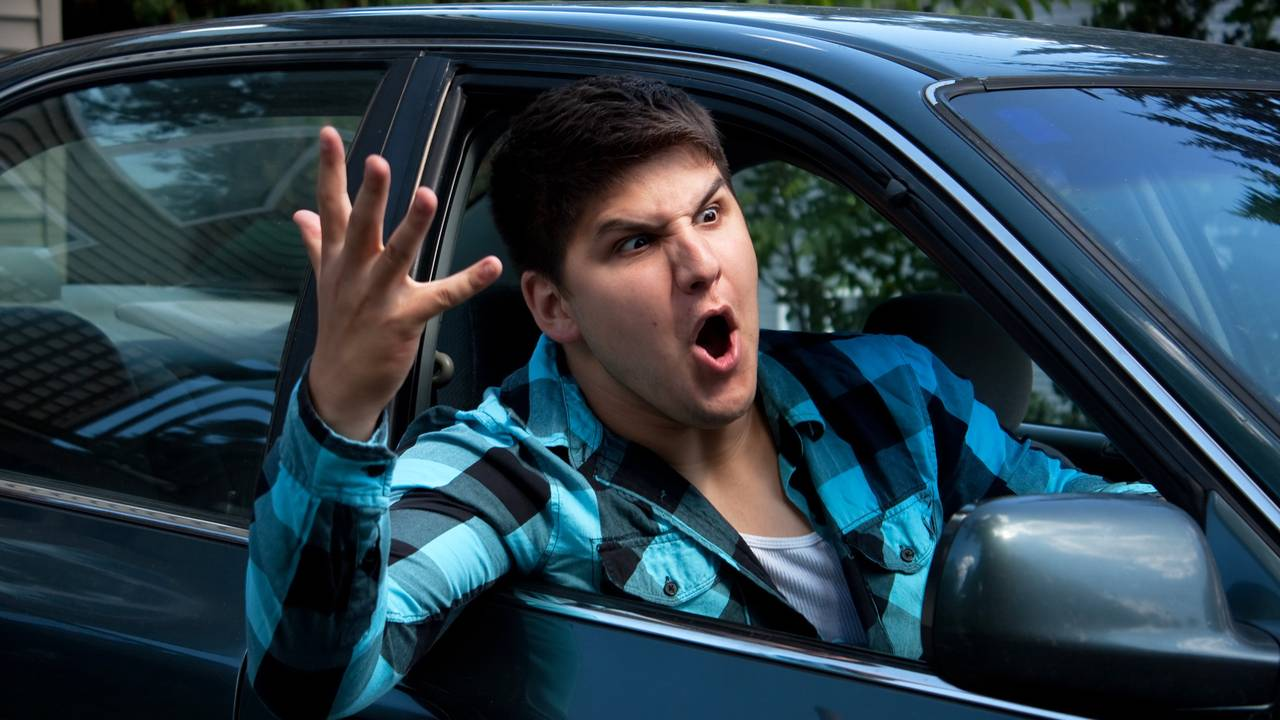 Angry young man driving expressing road rage