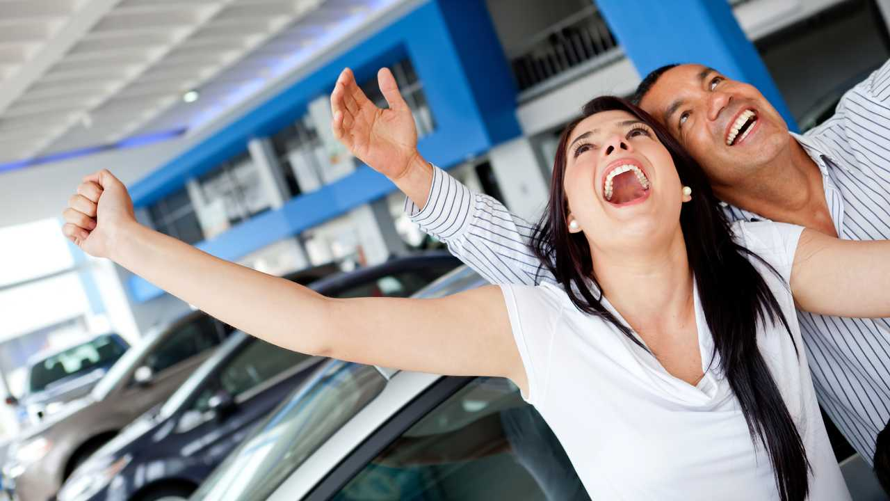 Excited couple buying a car at the dealer