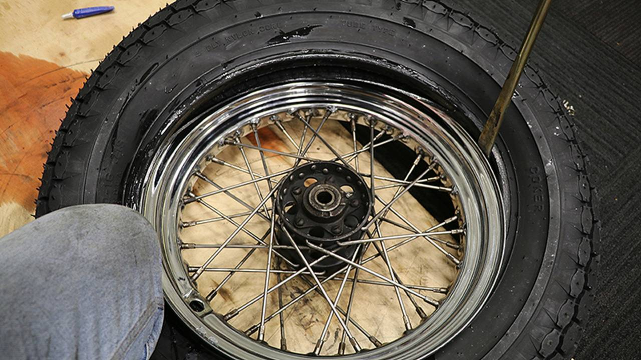 <em>Your knees make for a good set of tools for holding the new tire in place.</em>