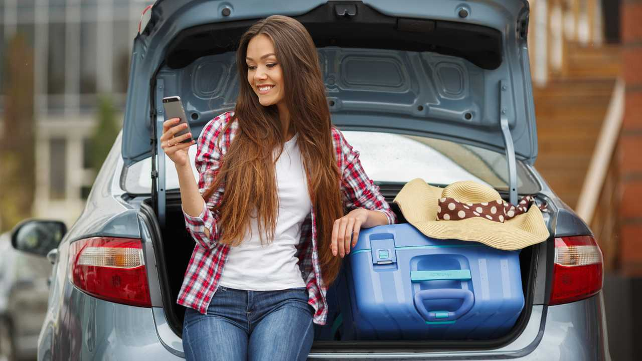 Young woman sitting in boot of car smiling and holding phone