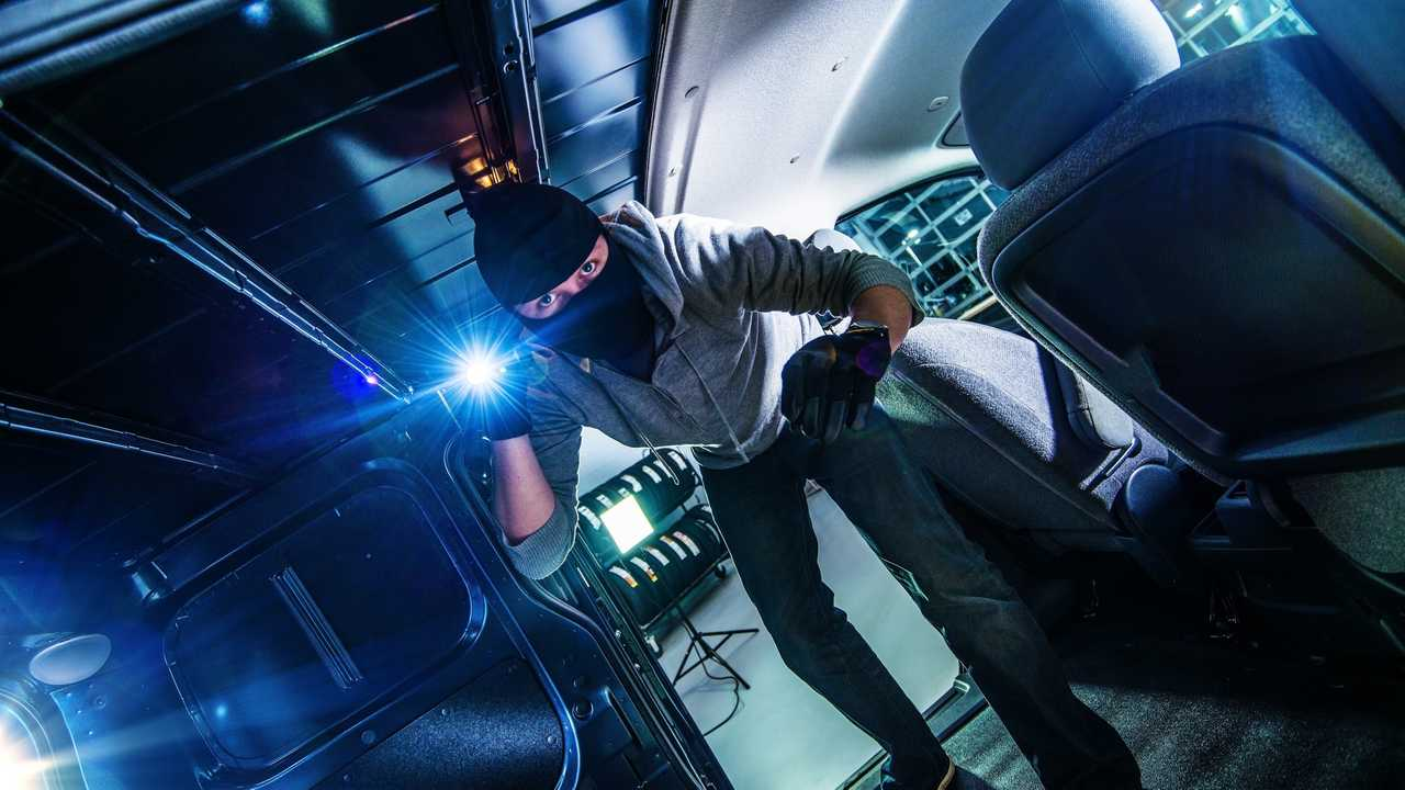 Thief with flashlight inside cargo van