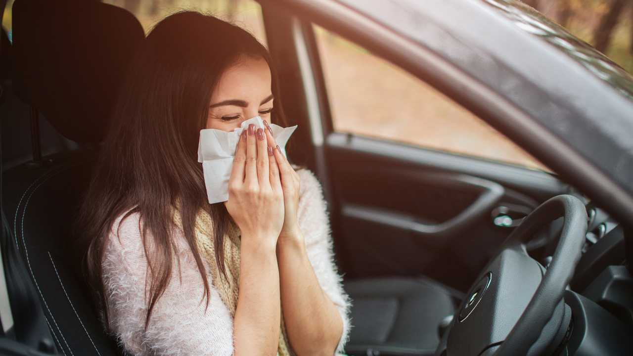 Woman driver blowing nose with handkerchief