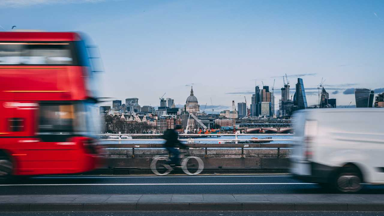 London skyline with moving traffic of bus van and bicycle in foreground