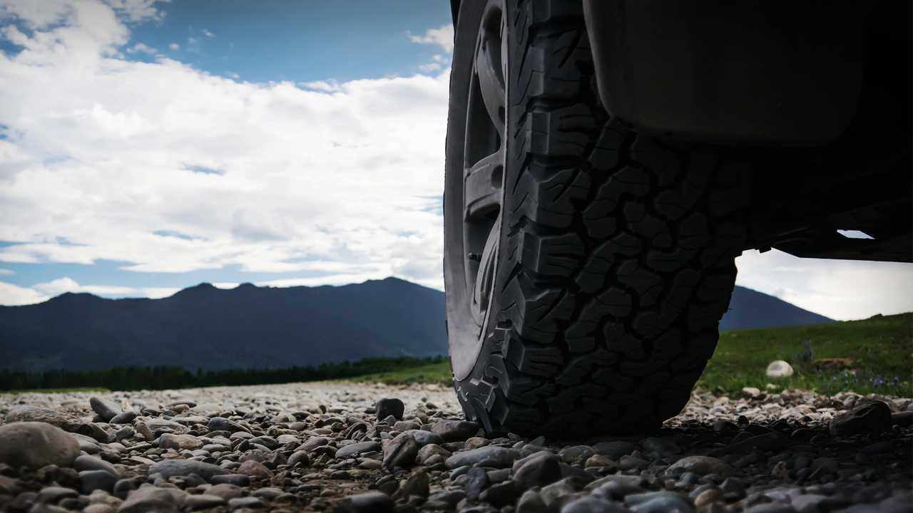 Wheel of SUV on gravel road