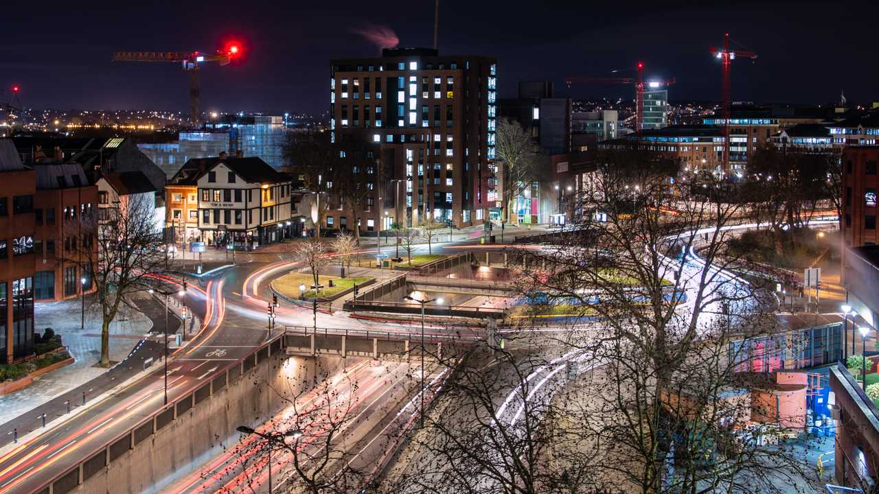 Traffic light trails through city at night in Bristol England