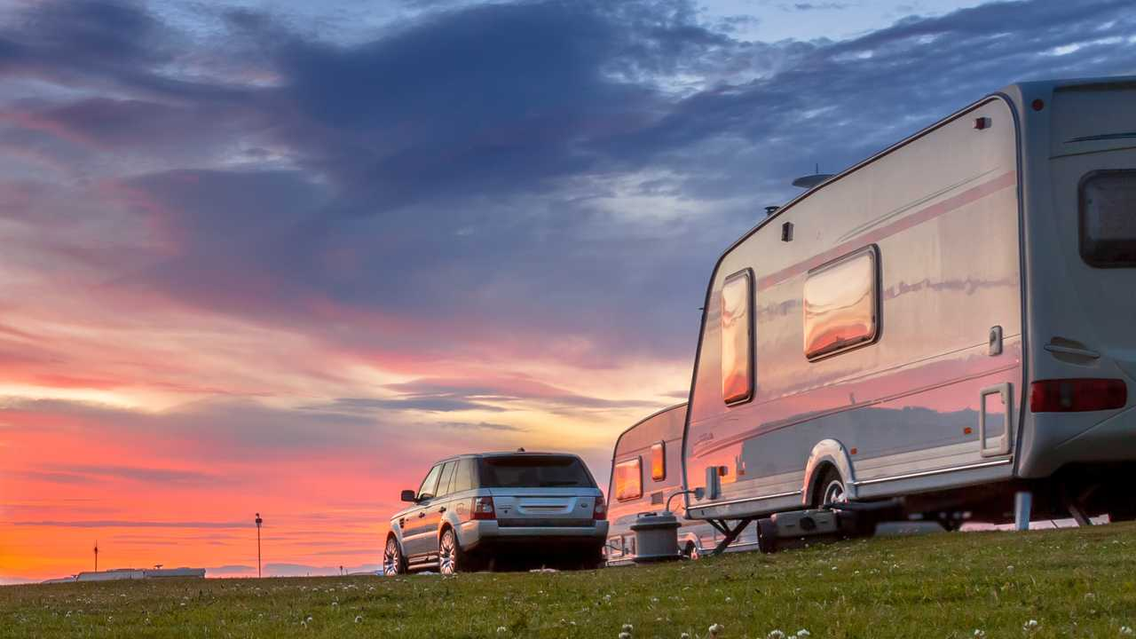 Camping caravans and cars parked under beautiful sunset