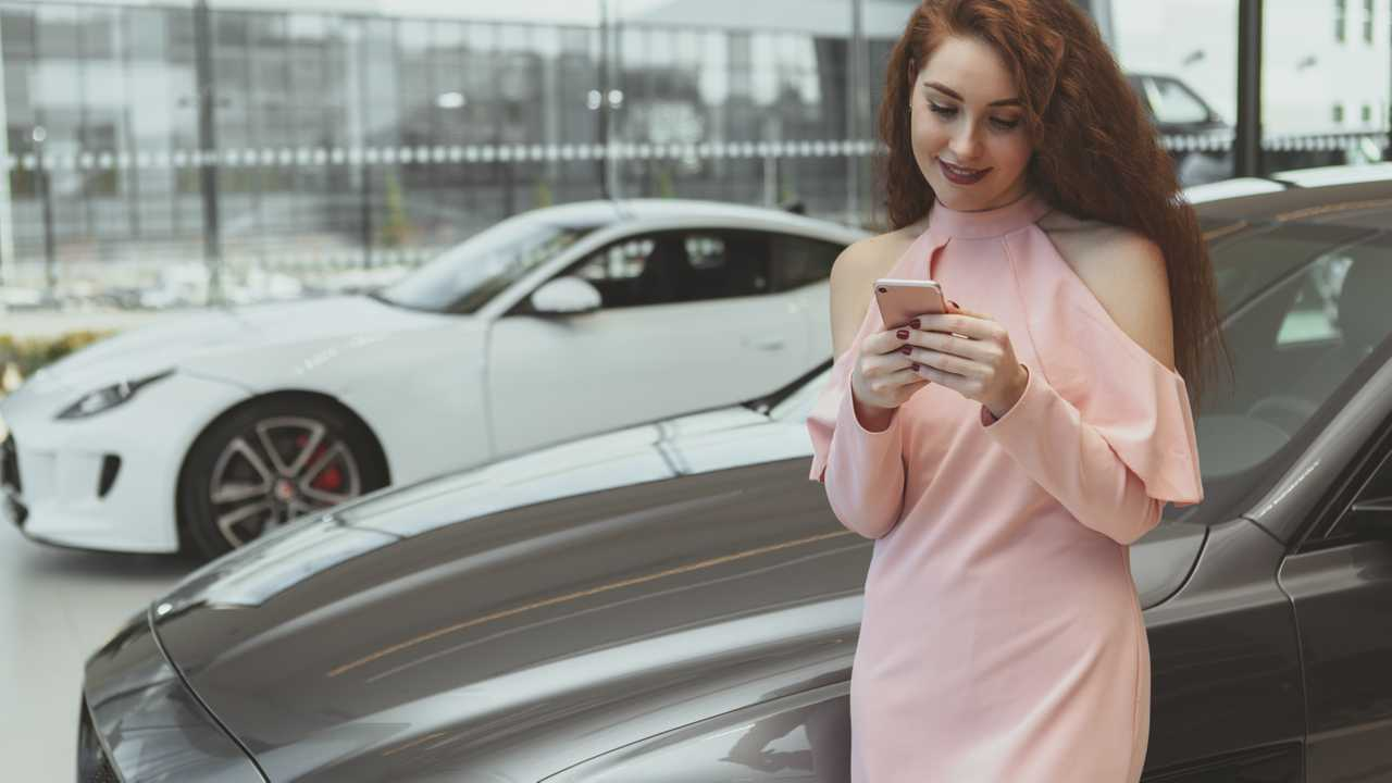 Woman on smartphone while buying car at dealership