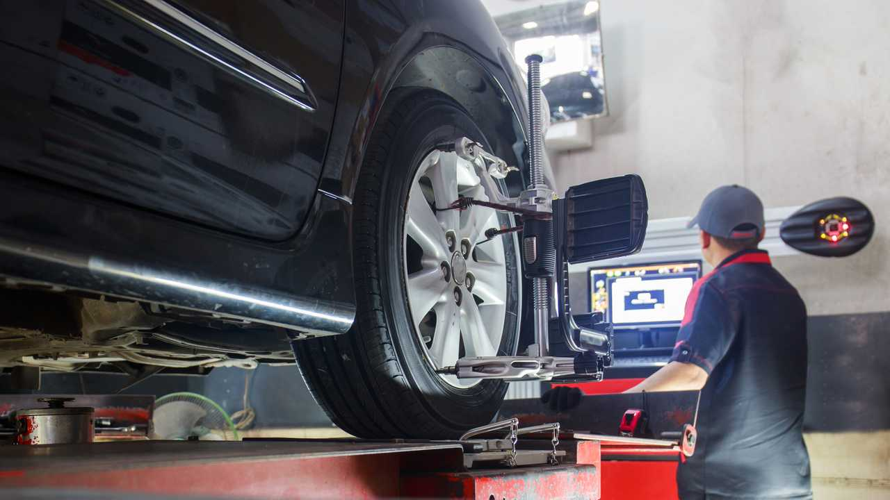 Mechanic performing car wheel alignment in service garage