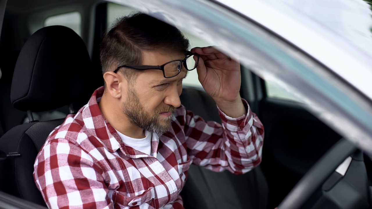 Tired driver taking eyeglasses off and squinting