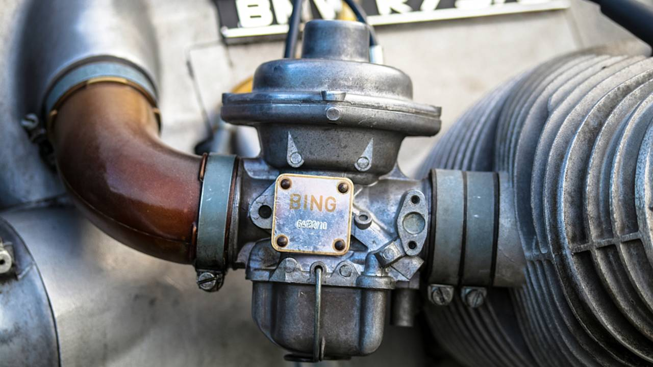 The round section at the top of the carburetor houses the diaphragm that creates the constant vacuum.
