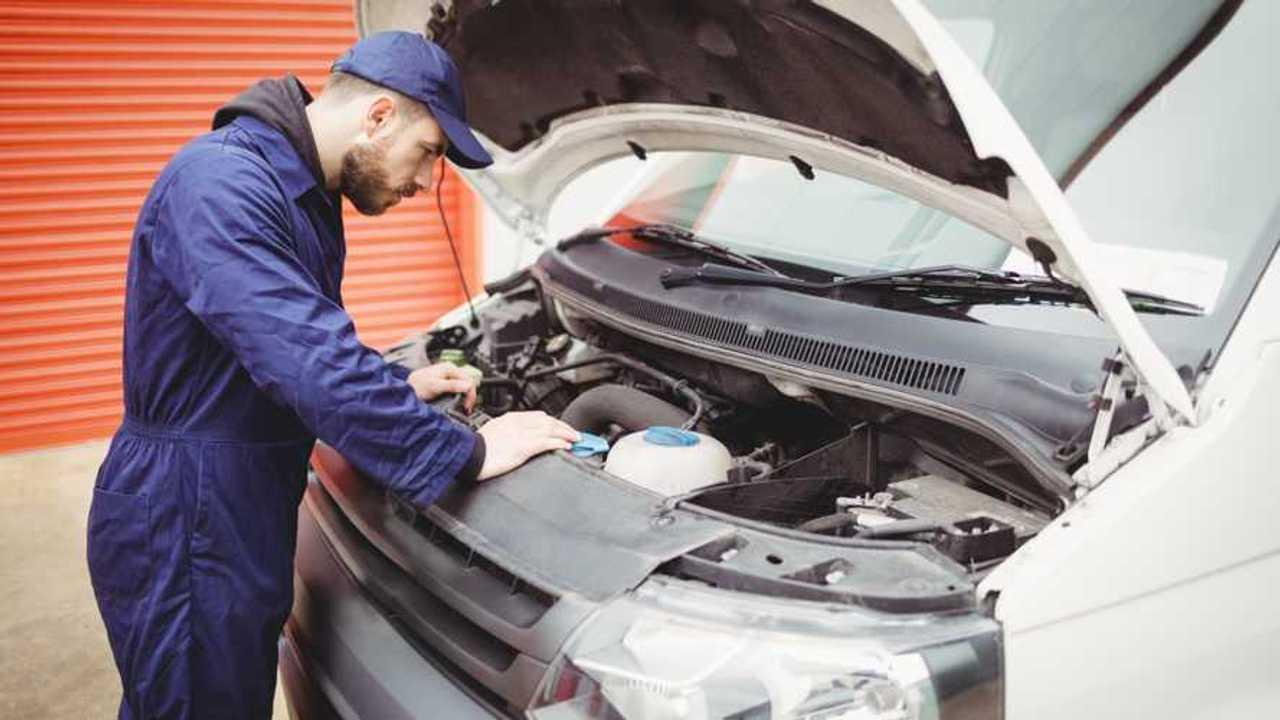 Mechanic fixing van engine