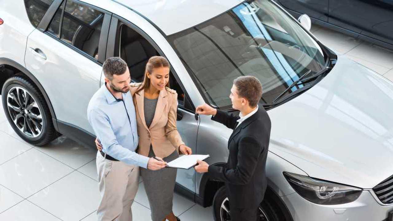 Car salesman is handing keys to buyer couple in showroom