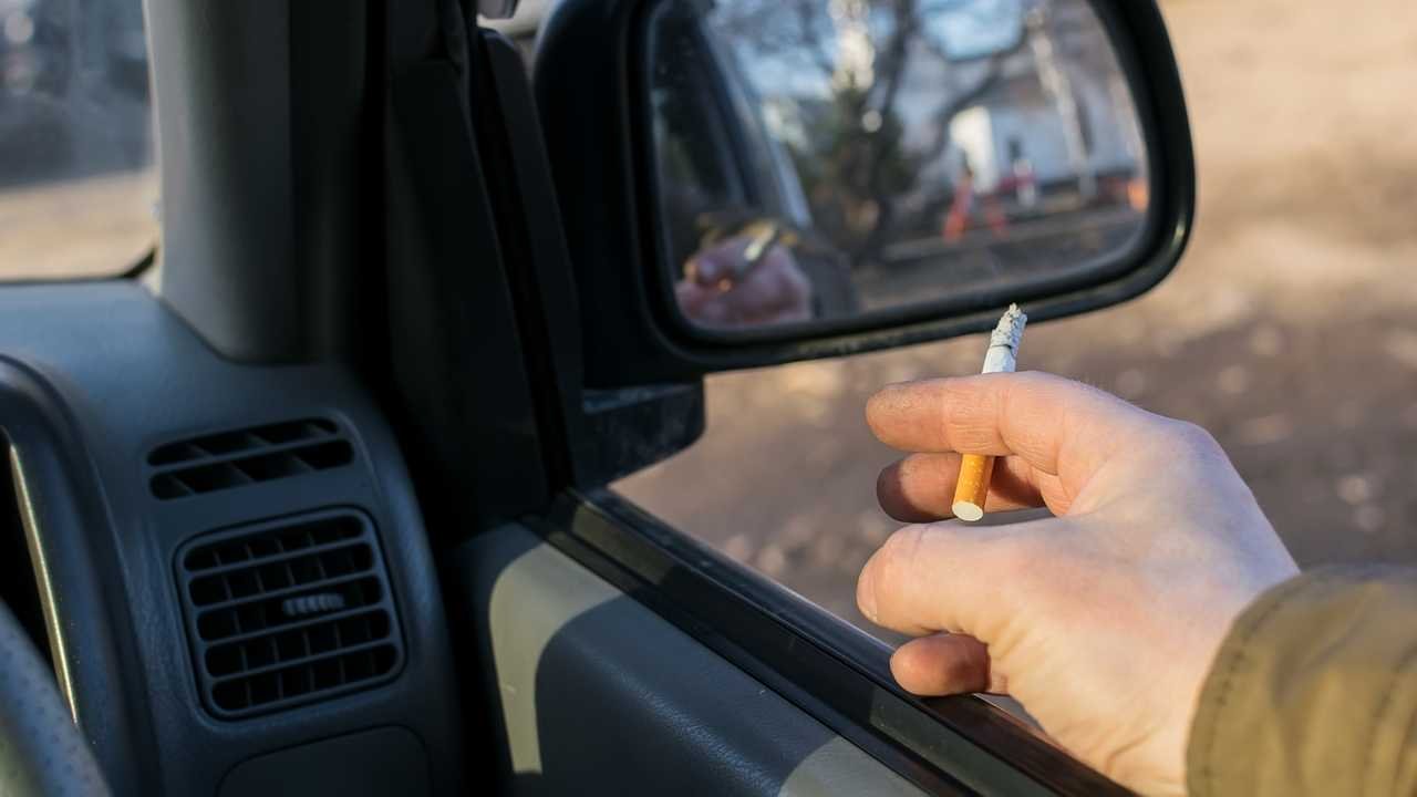 Driver smoking cigarette while sitting in parking lot