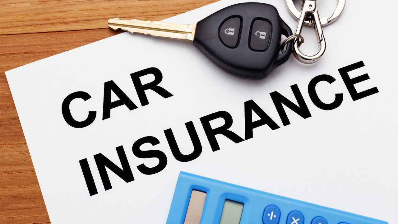 Car insurance with car key and calculator on table