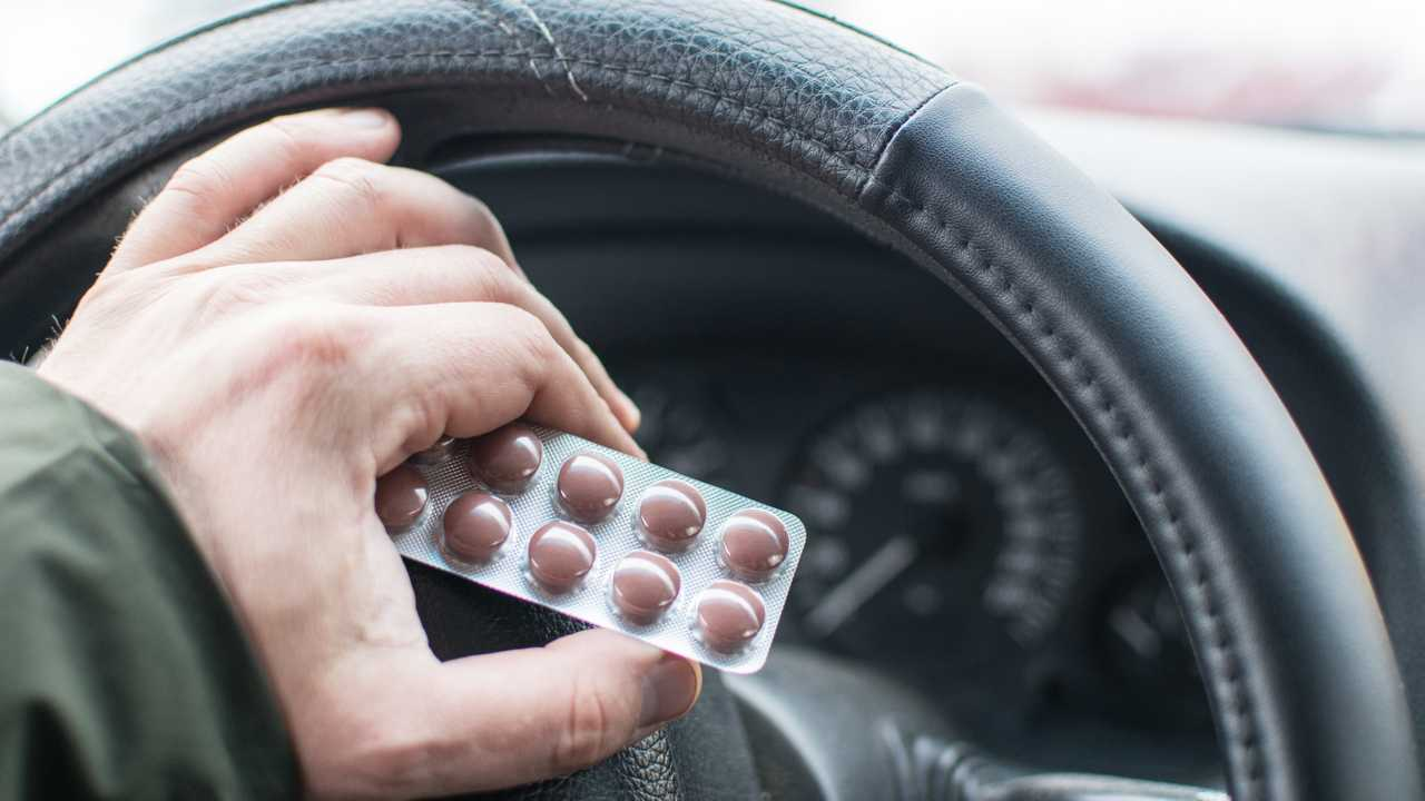 Man holds pill package on steering wheel