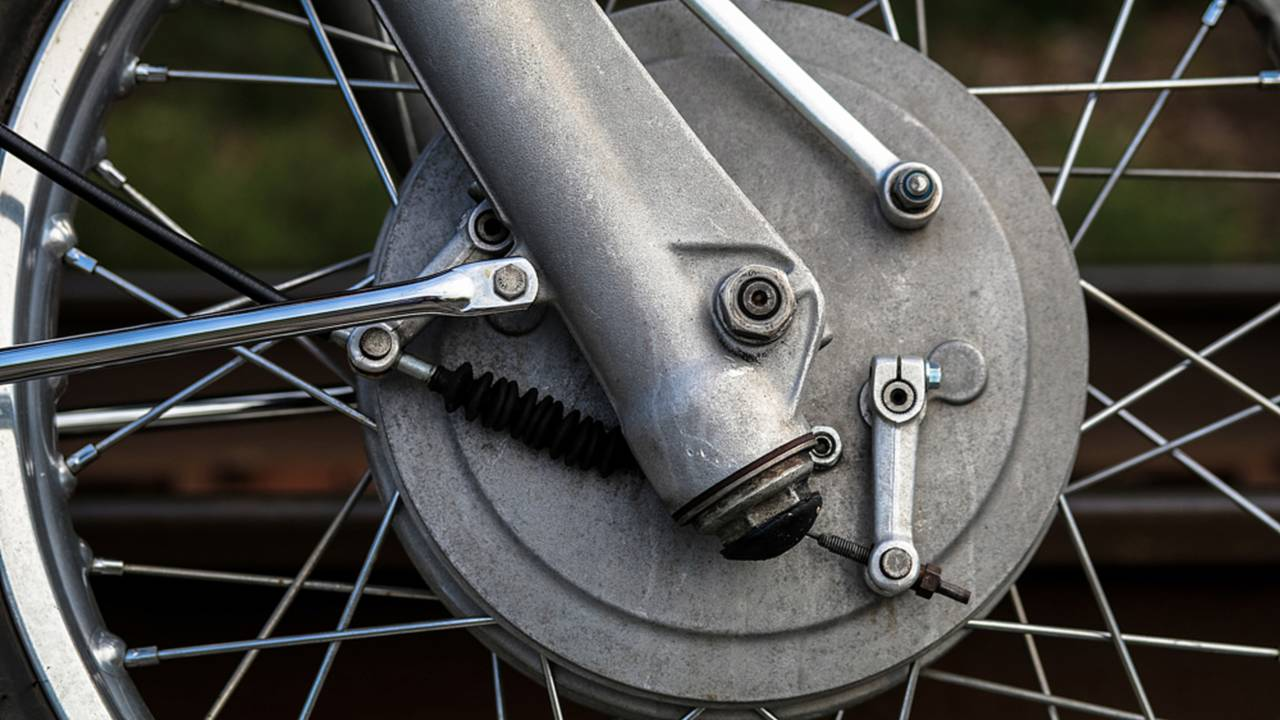 Two levers operate the dual brake cams simultaneously when the front brake lever is pulled.