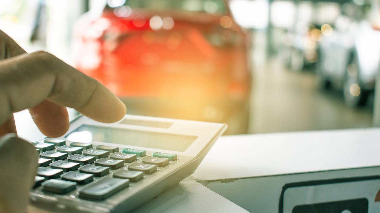 Man using calculator in car dealership showroom