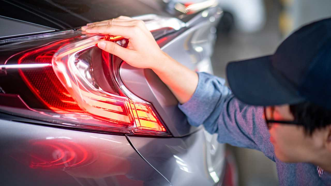 Mechanic checking taillight in auto service garage