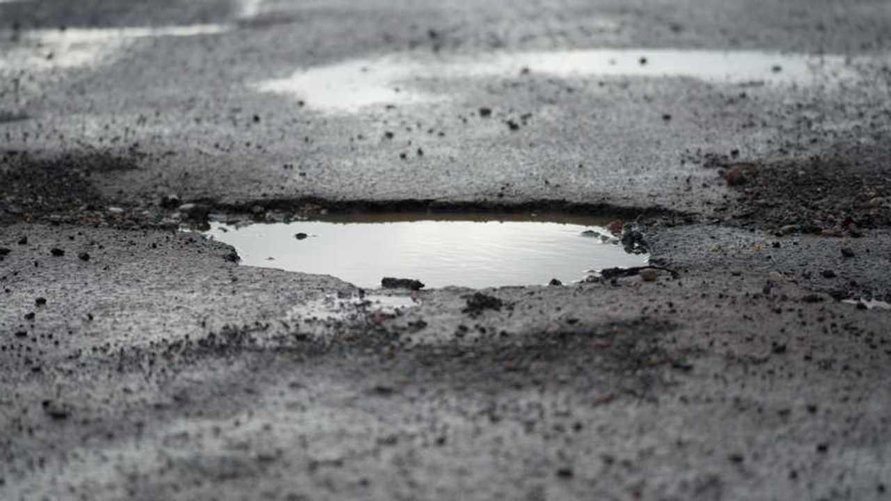 Potholes in road full of rain water in UK
