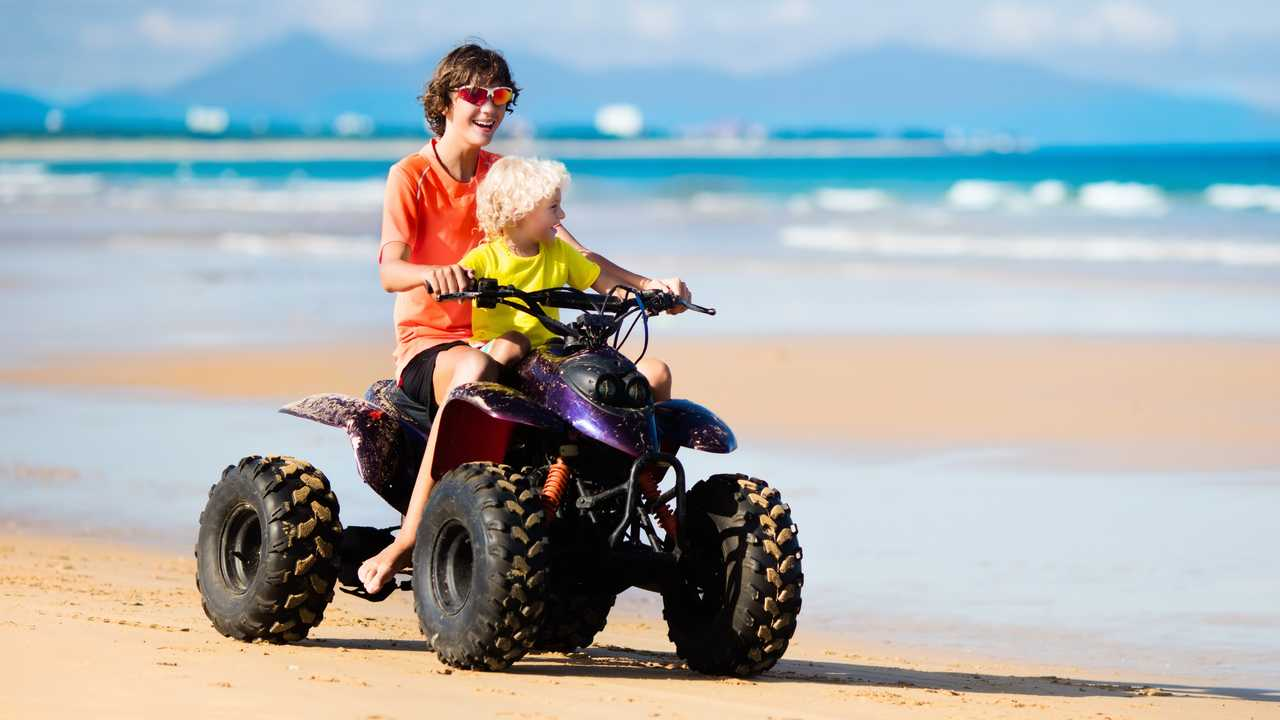 Teenager and his little brother riding quad bike on beach