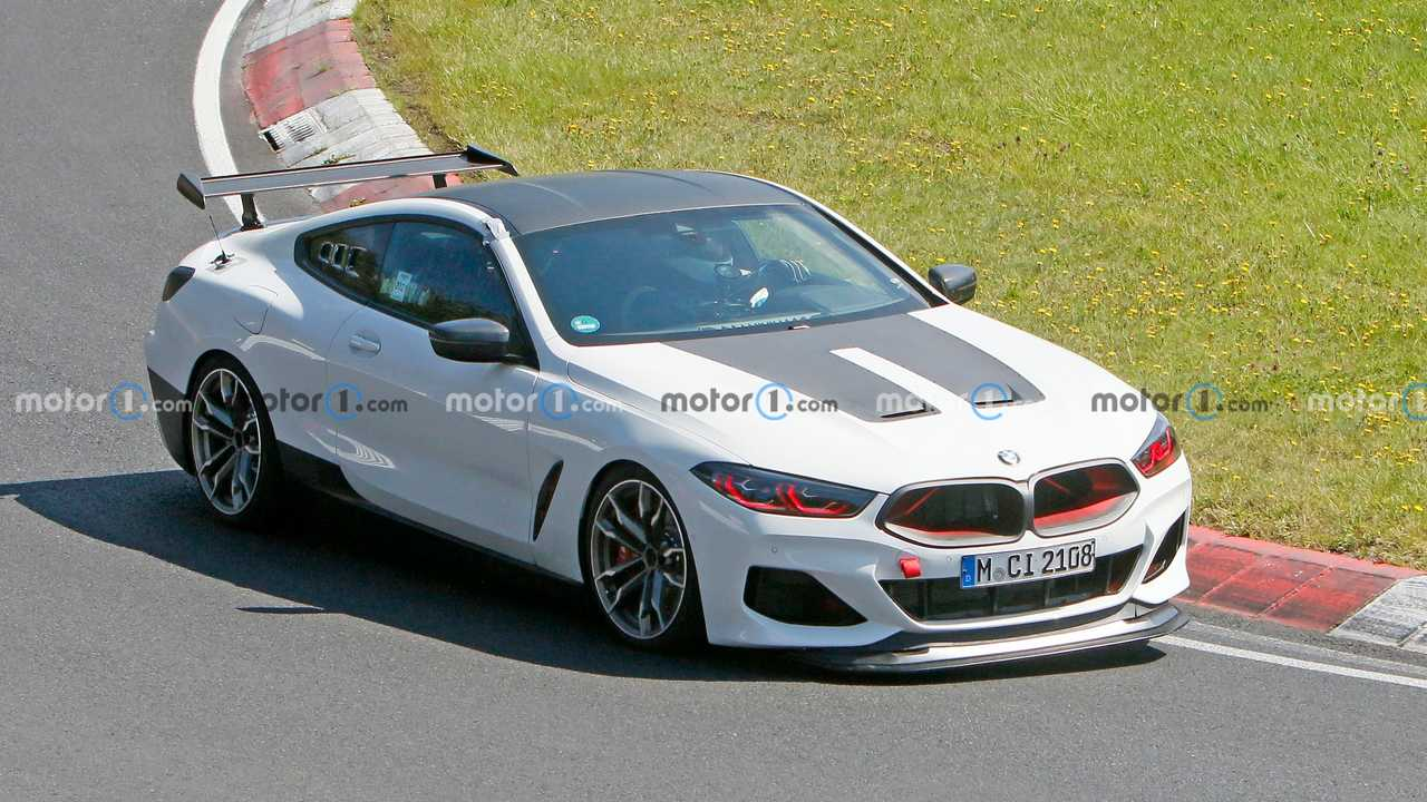 This BMW M8 test vehicle features an aggressive hood and red tinged headlights.