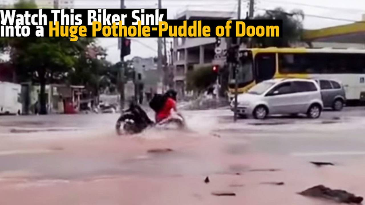 Watch This Biker Sink into a Huge Pothole-Puddle of Doom