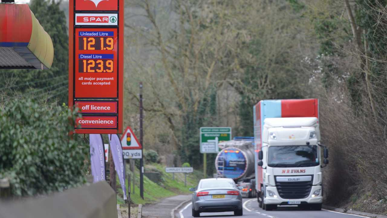 Fuel price sign at petrol station as traffic passes in Bath UK