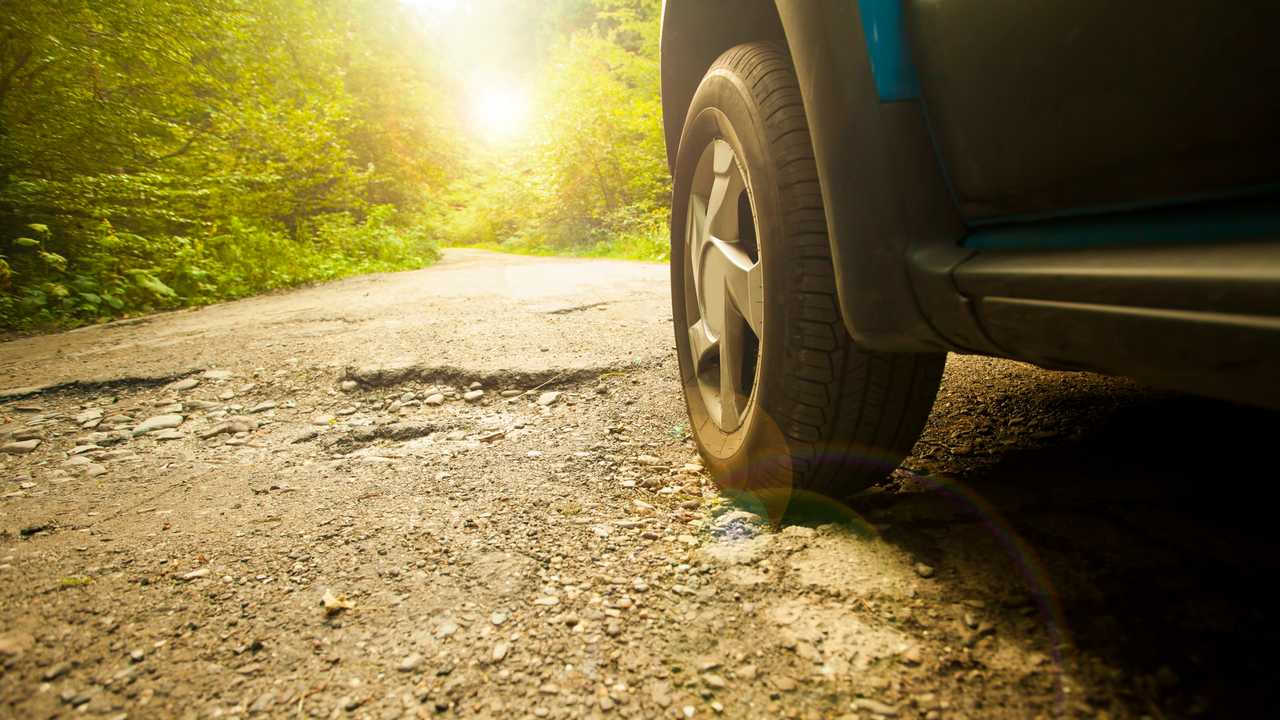 Car tyre and potholes in road